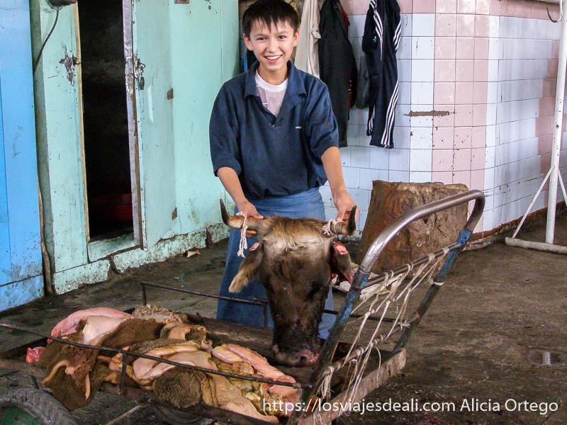 niño sosteniendo cabeza de vaca apoyada en un carro en la zona de carnicerías del mercado