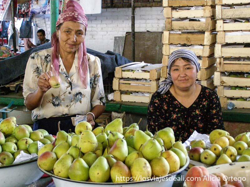 dos mujeres posando en su puesto de peras y manzanas