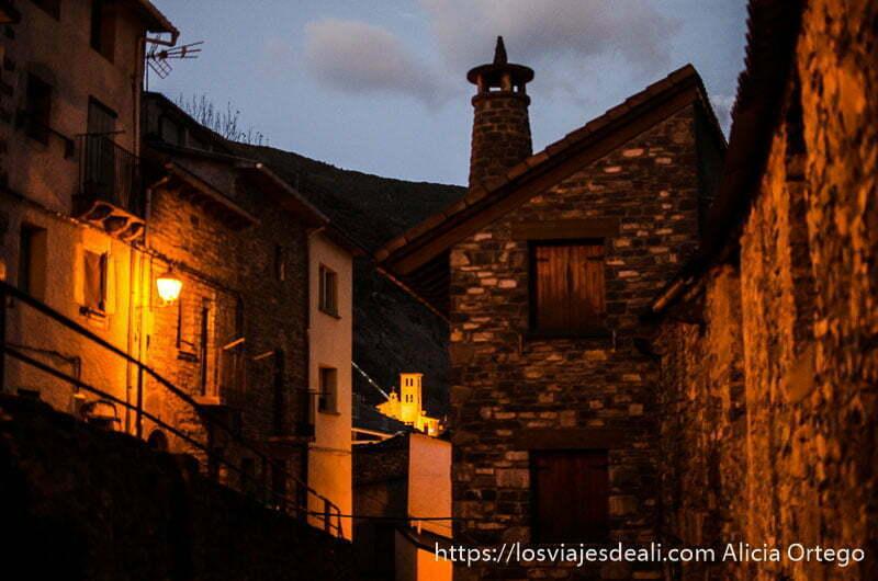 calle de pueblo del valle de tena con casas de piedra y al fondo iglesia iluminada