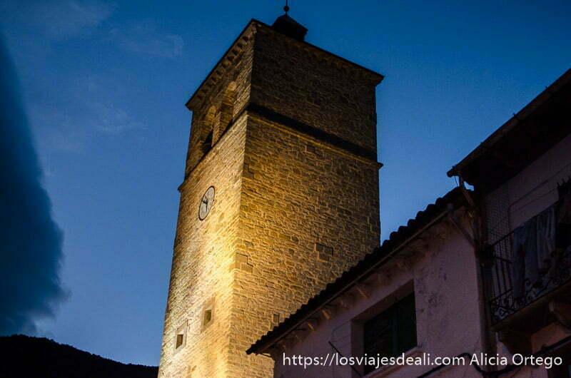 torre de iglesia con reloj iluminada en la hora azul