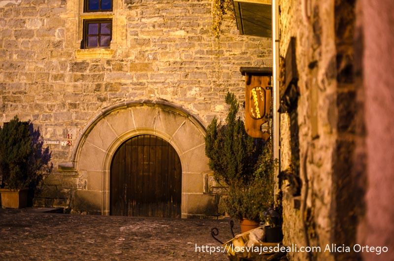 esquina de casa de piedra con puerta en forma de arco