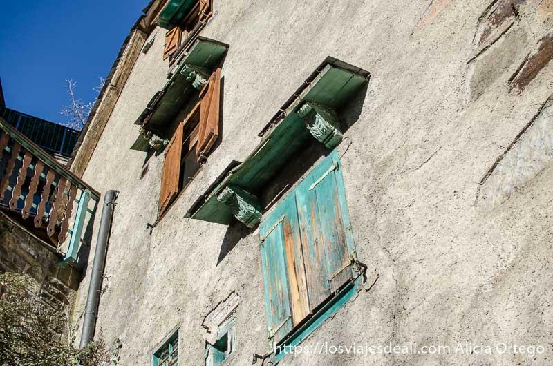 fachada de casa con ventanas de madera una pintada de verde