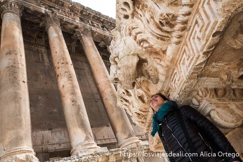 posando debajo de cabeza de león y con templo de grandes columnas al fondo en baalbek líbano