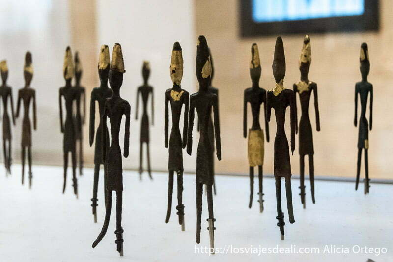 figuritas de bronce esquemáticas con restos de láminas de oro en el gorro, cuello y falda
