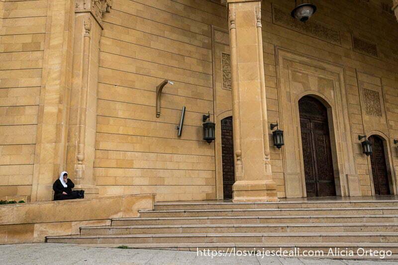 mujer sentada en el suelo junto a la entrada de la mezquita al amin de beirut