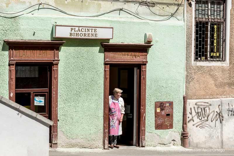 señora con delantal rosa asomada a la puerta de madera de su comercio tradicional