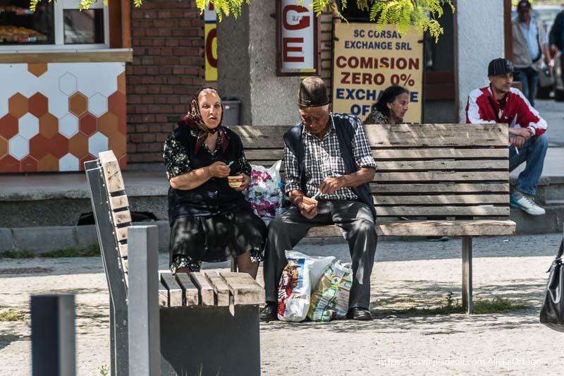pareja de ancianos gitanos comiendo un helado sentados en un banco de sibiu