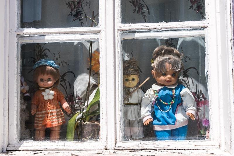 ventana con muñecas antiguas mirando a la calle