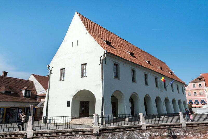 casa de paredes blancas con tejado rojo y soportales con arcos en sibiu