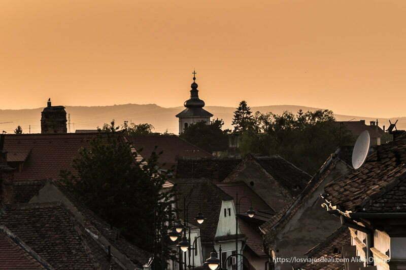 puesta de sol con torre de iglesia con tejado en forma de pequeño globo