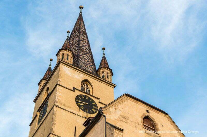torre de iglesia con tejas formando rombos y un reloj