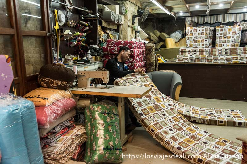 fabricante de colchones trabajando junto a máquina de coser