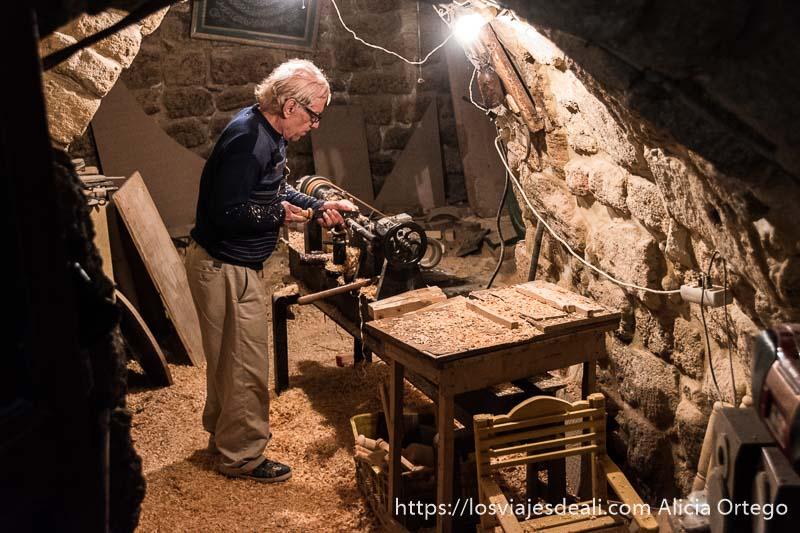 ebanista trabajando en su taller que es como una cueva con techo bajo de piedra