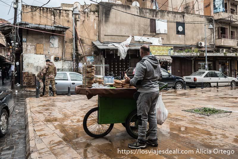 hombre vendiendo tortas de pan y al fondo un soldado