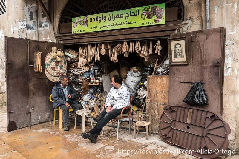 dos hombres sentados en una tienda de objetos de madera y mimbre en trípoli líbano