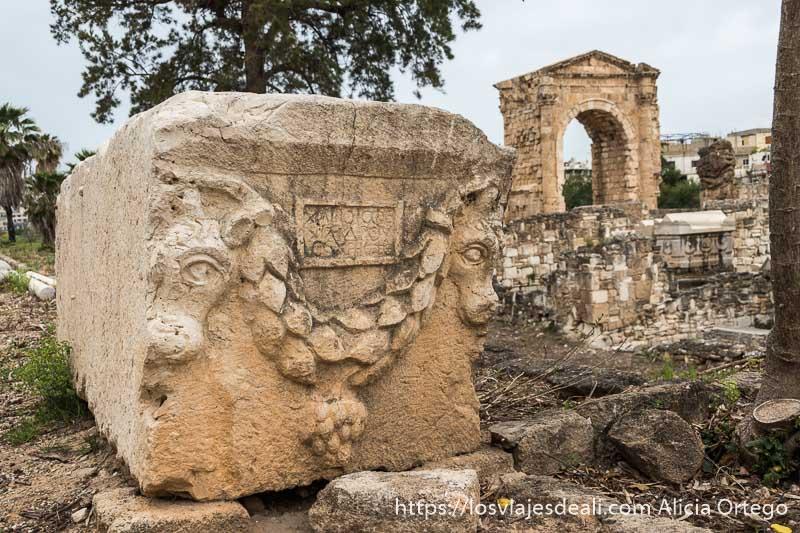 sarcófago de piedra con dos cabezas de toro y al fondo arco romano en la ciudad de tiro en líbano