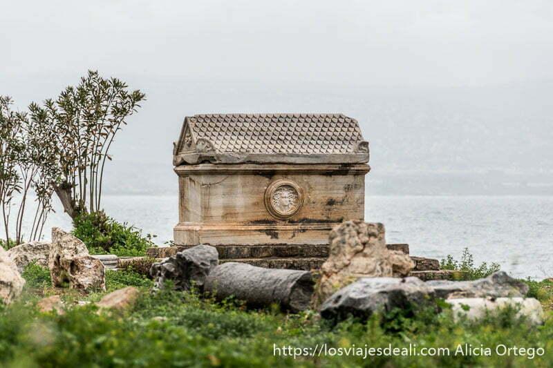 sarcófago con rostro de medusa en uno de sus lados y el mar al fondo en las ruinas de tiro