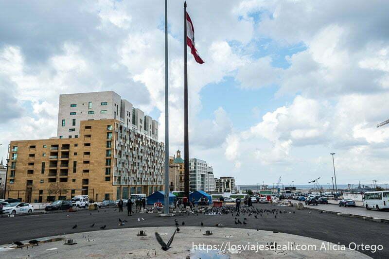plaza de los mártires con la bandera de líbano en un mástil y palomas