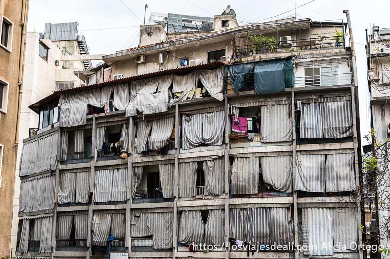 fachada llena de toldos a rayas muy sucios tapando los balcones en beirut