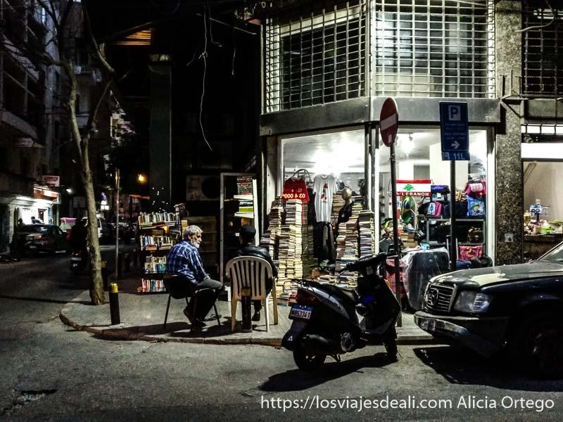 esquina con librería llena de pilas de libros y dos hombres sentados hablando por la noche en beirut