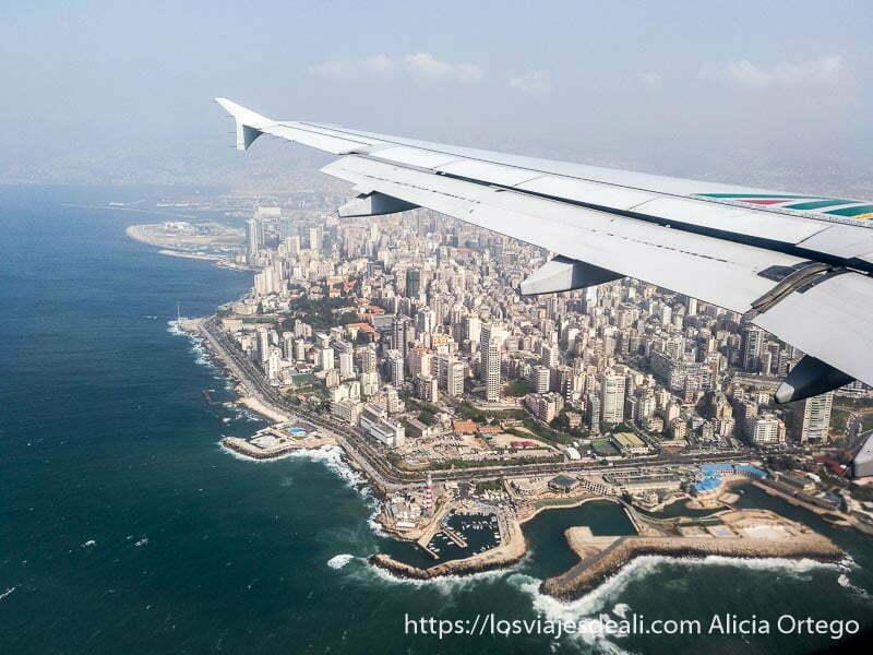 ala del avión con la ciudad de beirut llena de rascacielos y el mar