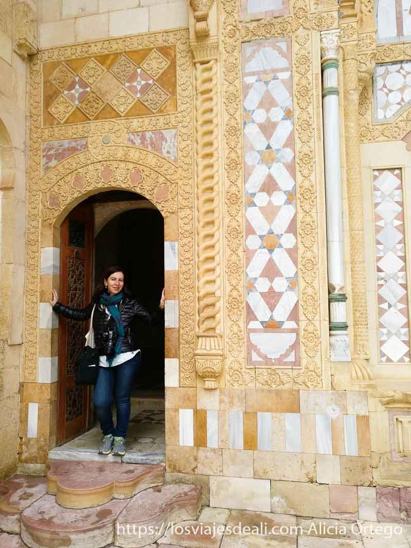 posando en la puerta de un palacio con mármoles en la fachada en líbano