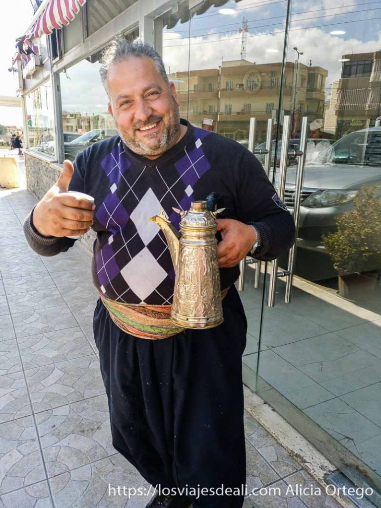 señor con pantalón turco y cafetera ornamentada sonriente ante la cámara y levantando pulgar