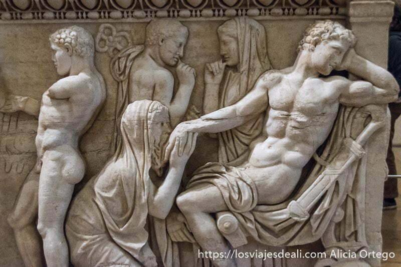 relieves de un sarcófago donde se ve un hombre atlético sentado en una silla y una mujer cubierta con un manto besándole la mano arrodillada
