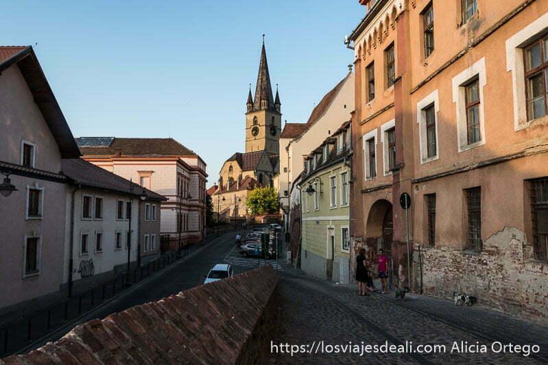 calle con dos niveles y al fondo iglesia con tejado acabado en punta