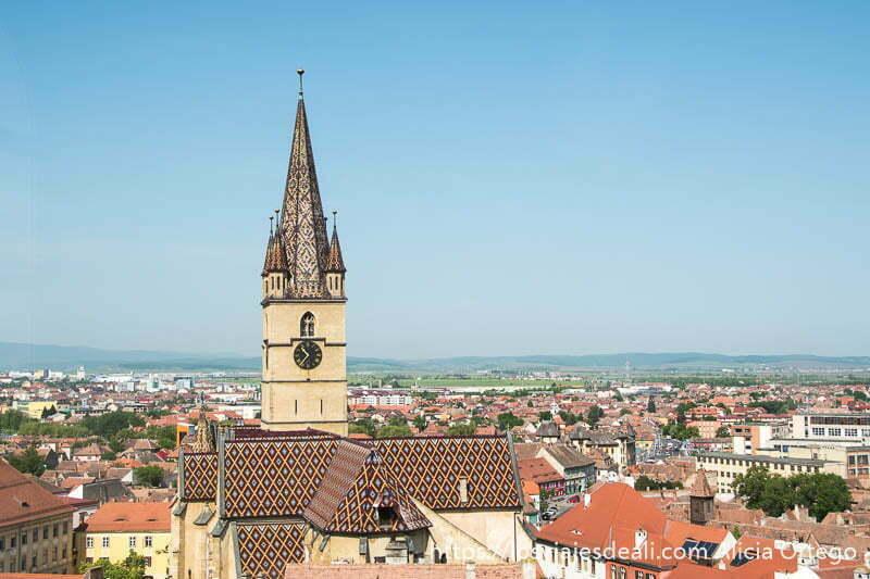 torre de iglesia con tejas de colores sobre los tejados de sibiu