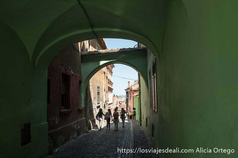 pasaje con arcos pintado de verde y calle empedrada por donde van cuatro niñas con sus mochilas del colegio