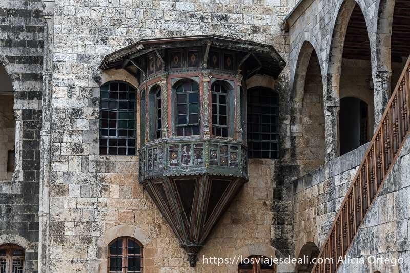balcón de madera con ventanas de colores adosado a muro de piedra en el palacio de beiteddine en la excursión a los alrededores de beirut