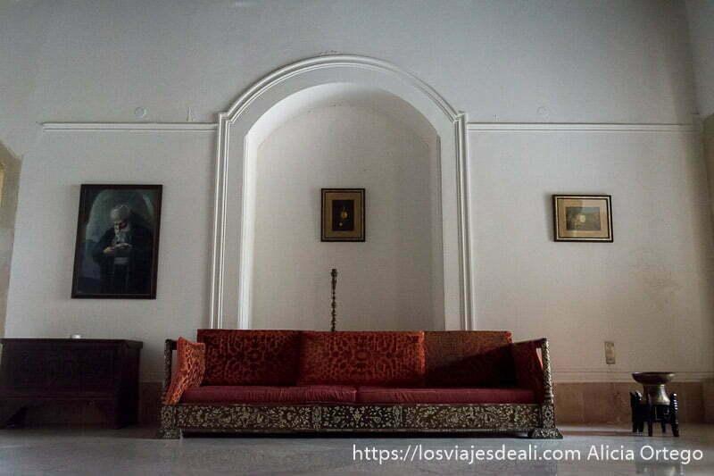 sala del palacio con gran sofá rojo y pared blanca con tres cuadros n la excursión a los alrededores de beirut