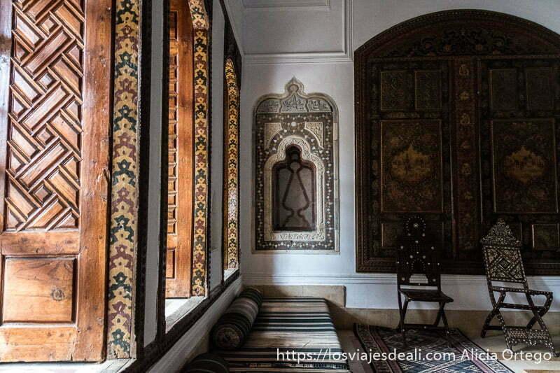 ventanas de madera de colores y sofá debajo en el palacio de beiteddine en la excursión a los alrededores de beirut