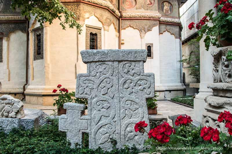 lápida antigua con dibujos florales y geranios rojos a un lado en claustro de iglesia ortodoxa
