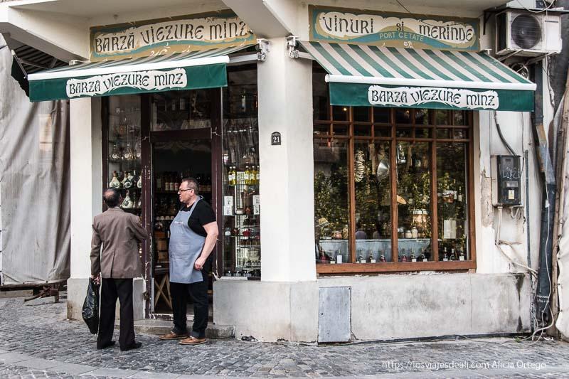 esquina con tienda de productos tradicionales y el tendero con delantal hablando con un cliente