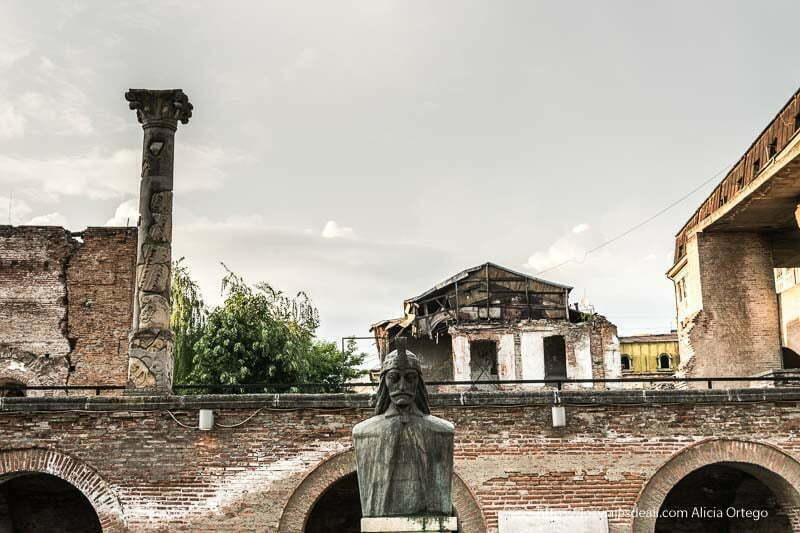 busto de vlad tepes con columna corintia y edificio en ruinas detrás en el centro de bucarest