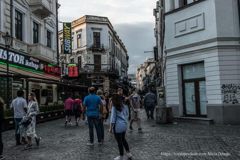calle de bares y restaurantes del centro de bucarest con gente yendo y viniendo