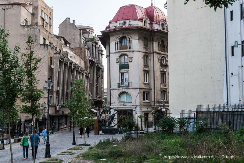 calle del centro de bucarest con edificio con tejado rojo