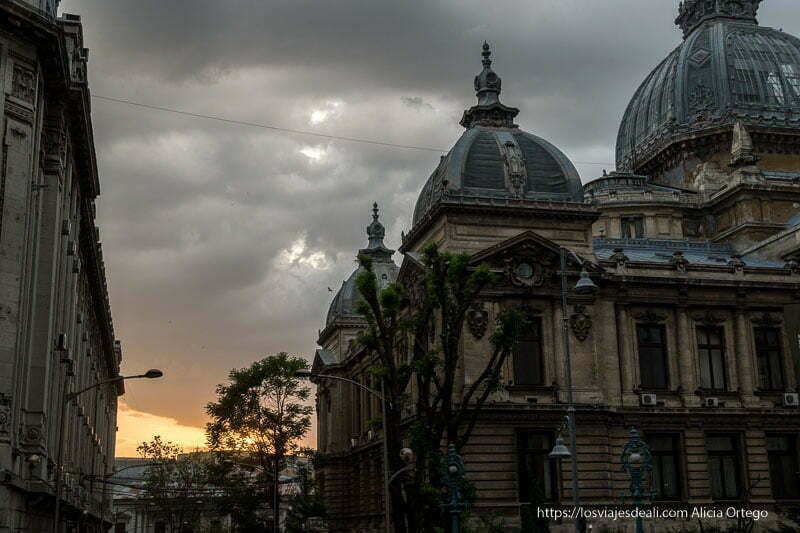 atardecer muy nublado sobre edificio neoclásico con cúpula de cristal en el centro de bucarest