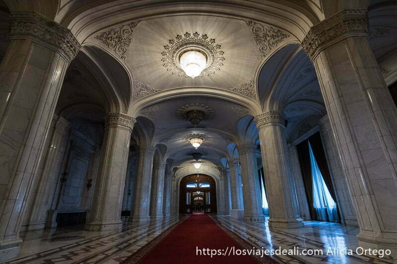 pasillo de grandes dimensiones con columnas y techos de mármol y gran alfombra roja en el parlamento de bucarest