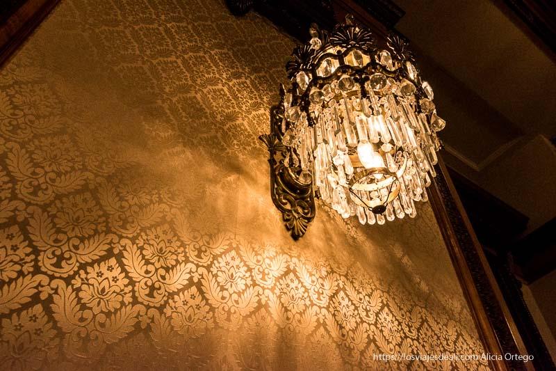 lámpara de cristal y hierro proyectando luz sobre pared empapelada con dibujo floral