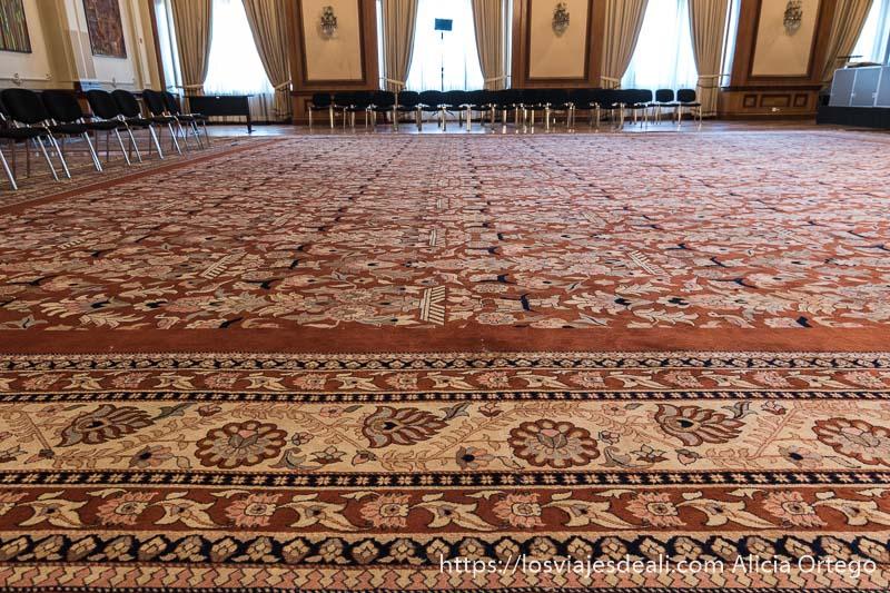 alfombra de colores rojos y rosas en una de las enormes salas del parlamento de bucarest