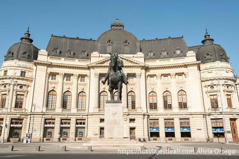 edificio neoclásico con estatua ecuestre delante en la calle victoria de bucarest