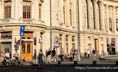 gente andando junto a edificio neoclásico iluminado por luz cálida en bucarest