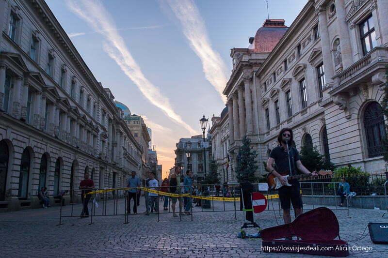 calle con edificios neoclásicos y nubes haciendo rayas en el cielo del atardecer y un músico tocando la guitarra en primer plano