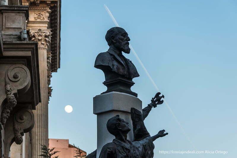 busto de bronce y estatua de otro levantando la mano hacia el cielo y luna llena al fondo en bucarest