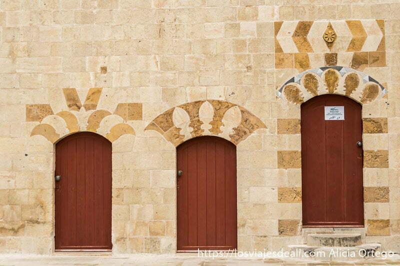 tres puertas rojas en una pared de color beige en deir el qamar en la excursión a los alrededores de beirut
