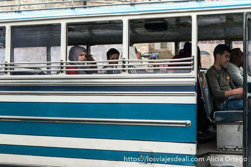 autobús escolar de color azul y blanco con dos adolescentes dentro con velo y un niño pequeño en deir el qamar excursión a los alrededores de beirut