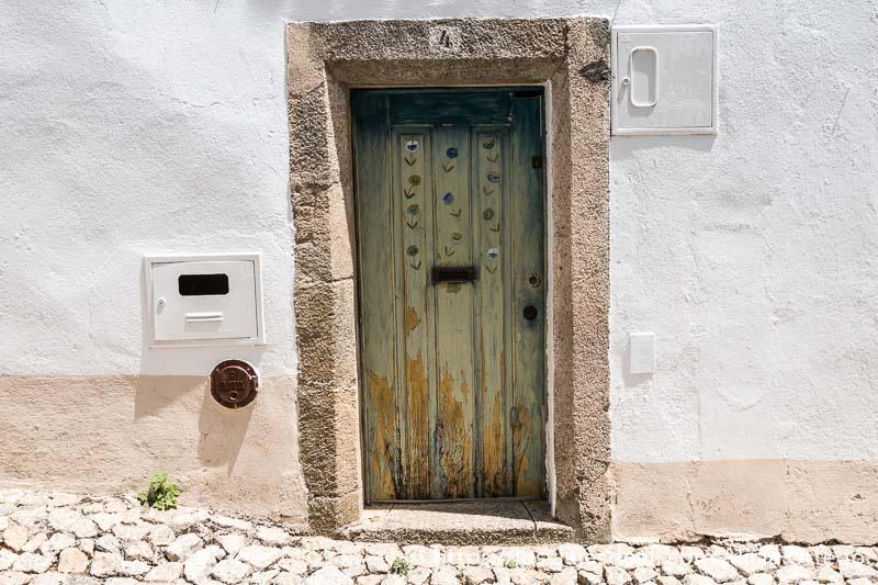 puerta de madera pintada con flores y marco de piedra en muro blanco en el pueblo de marvao portugal